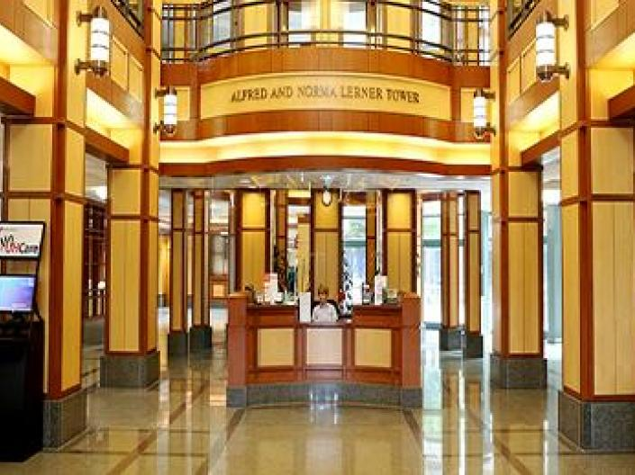 Image of lobby of Alfred and Norma Lerner Tower.  The area is lit up with bright yellow lights, with small plants and kiosks on both sides.  There is old fashioned lighting and a second floor with a railing above.  The receptionist is seated in a wood panelled area in the center