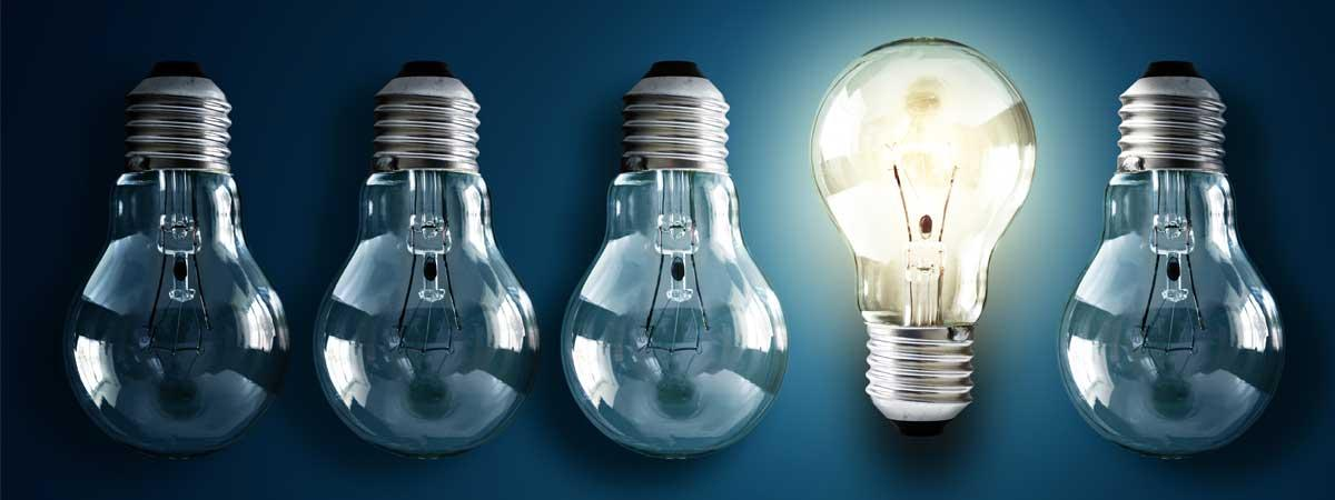 A stock image of four dim lightbulbs upside down and one bright right-side up