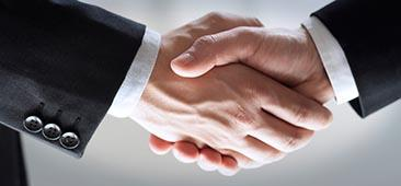 Picture of close up of the hands of two professionals in suits shaking each others hands