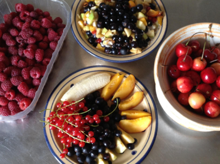 A selection of health foods consisting of a carton of raspberries, bowl of cherries, bowl of assorted fruits, and a bowl of fruit salad topped with blueberries