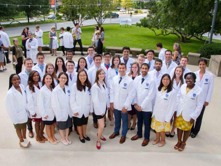 A group of 30 medical students stand together in their new white coats at the CWRU Medical School White Coat Ceremony