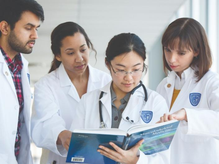 Medical students reading through a textbook together