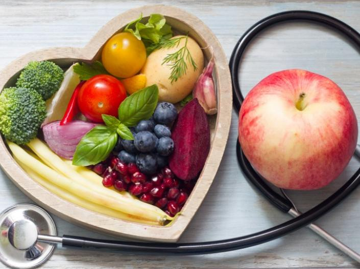 Fruit and vegetables in a heart shaped bowl next to an apple sitting on a stethoscope