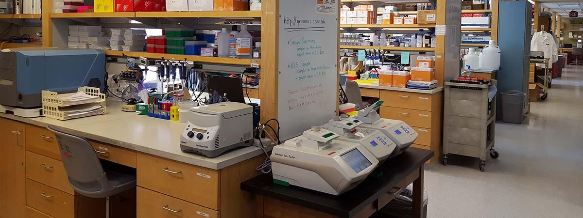 Picture of a laboratory with many aisles containing supplies with three pieces of highly technical lab equipment in the foreground