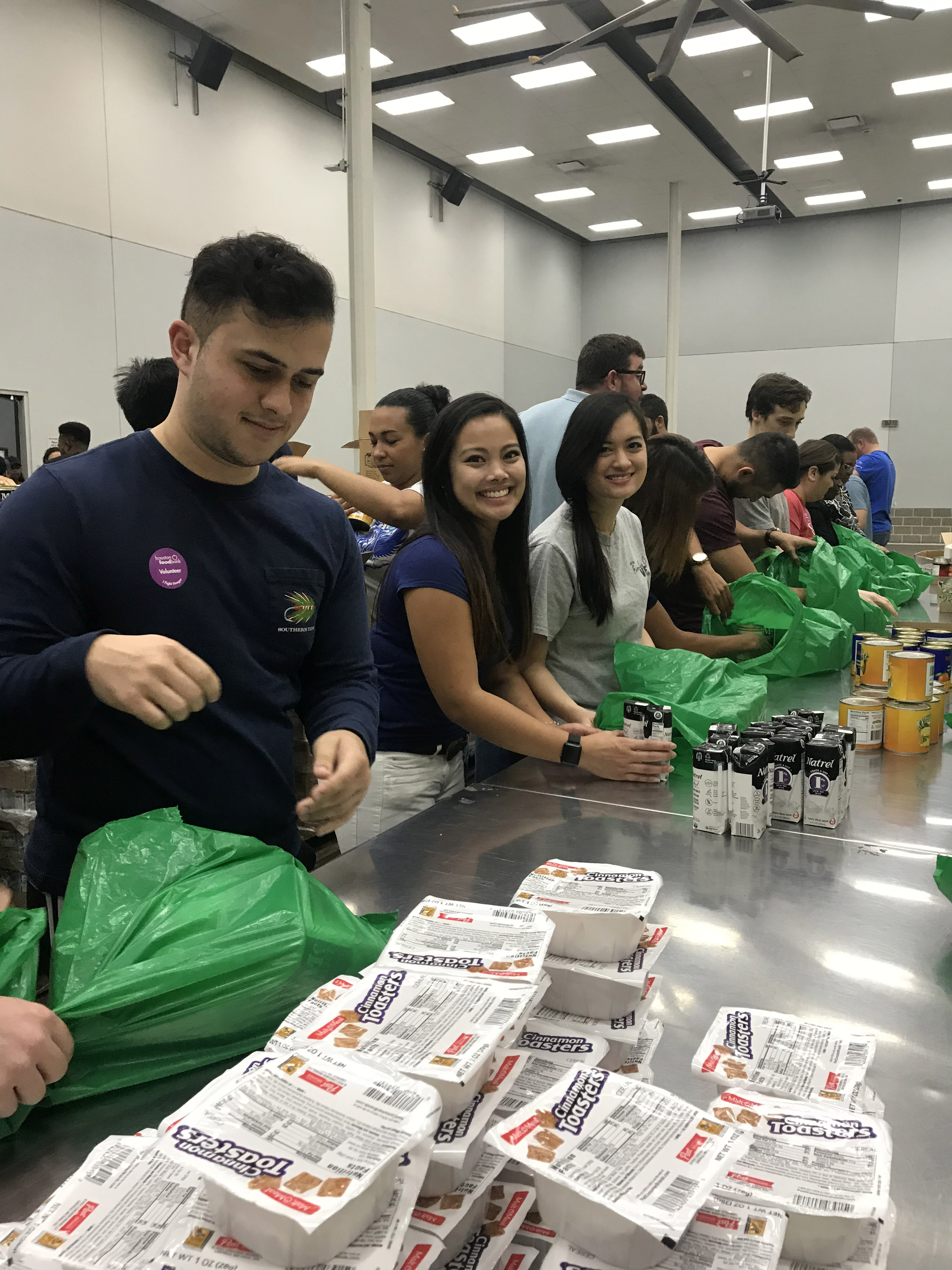 CWRU MSA Houston students in assembly line for packing bags