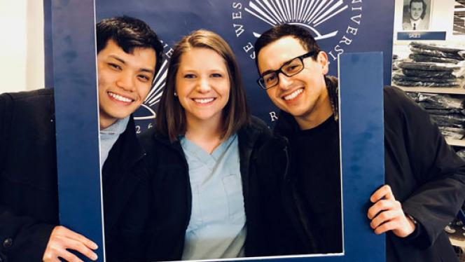 Two male students and one female student posing with CWRU open frame prop