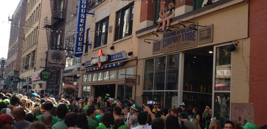 Image of crowd during Saint Patrick's Day in downtown Cleveland with House of Blues sign in the right midground and House of Blues Company Store sign in the right foreground