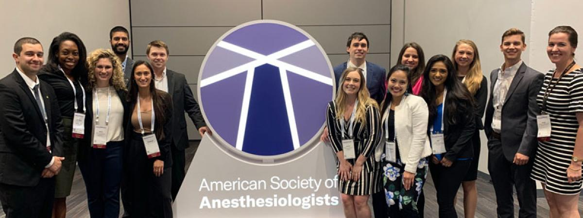 Students gathered around a sign for the American Society of Anesthesiologist Assistants