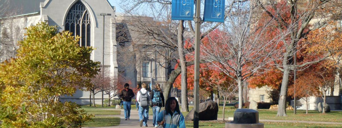 Female Case Western Reserve University student walking with three students behind her