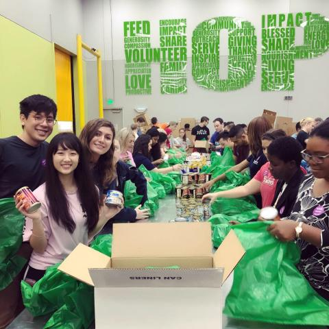 CWRU MSA Houston students packing green bags of food