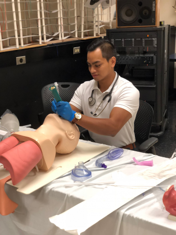 Student working on intubating task trainer