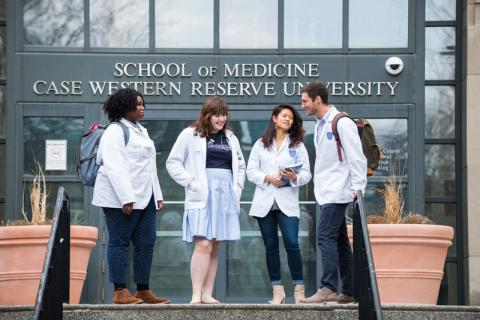Three female students and one male student standing in front of Case Western Reserve University School of Medicine doorway