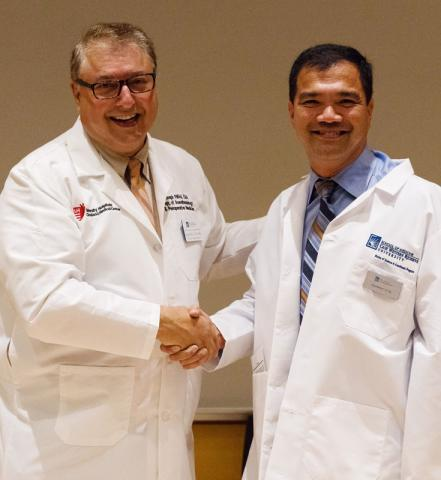 Two male certified anesthesiologist assistants in white coats shake hands
