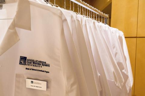 Row of white anesthesiologist assistant student coats on hangers with School of Medicine Case Western Reserve University embroidered on front with name tag