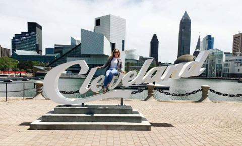 Female masters student sitting on Cleveland sign in Cleveland, Ohio