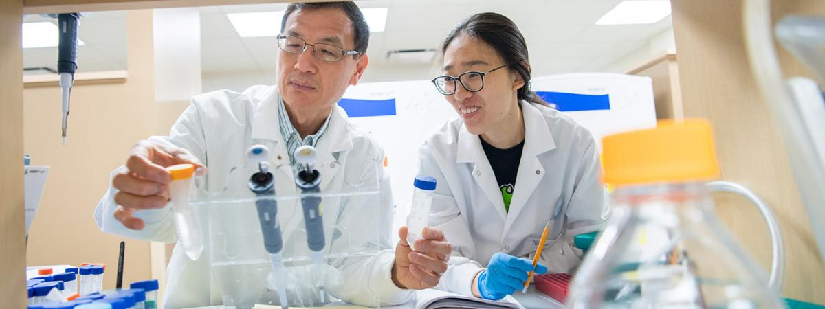Lin Mei with a student in the lab