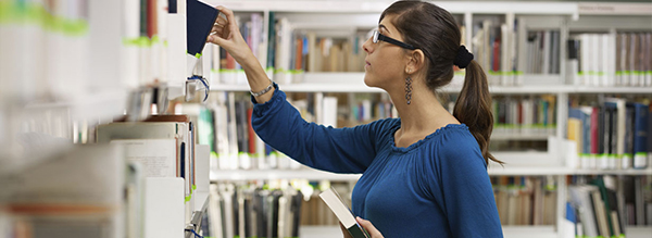 Image of student wearing blue and black glasses, surrounded by white library shelves in the background and to her left.  she has a black book in her left hand, and is taking a black book off the shelf on the left.