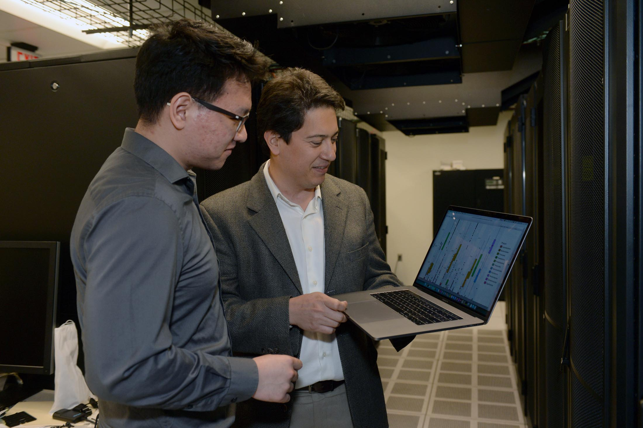 A professor and a student look at data together on a laptop.