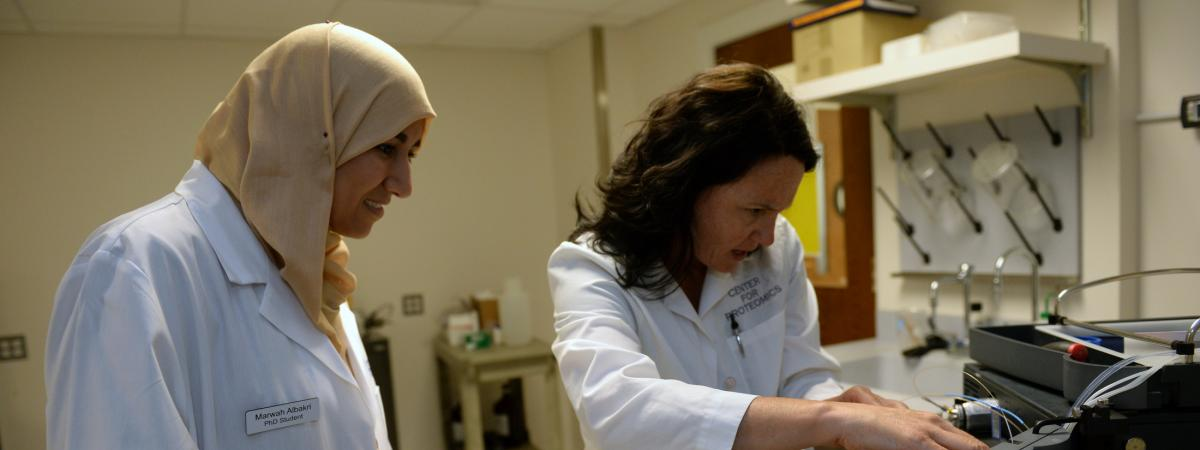 Two women wearing white coats work with scientific equipment.