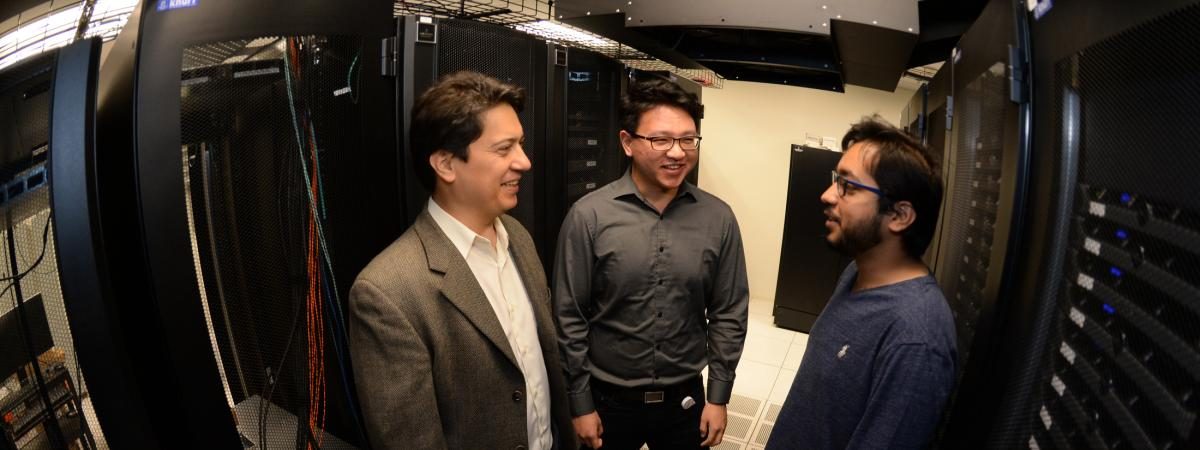Three men stand in an aisle of a server room while talking and smiling.