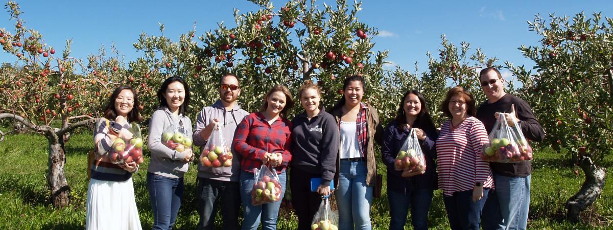 A group of 10 people stand in an apple orchard holding fresh-picked apples.