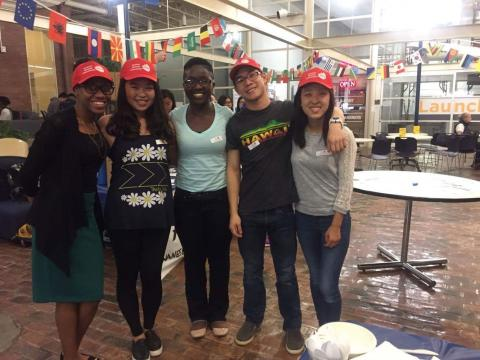 Image of five students, four of whom are wearing red hast with visors, from Case Western Reserve University's culture-based clubs in a student area decorated for Student Dietetic Association's Multicultural Food Day with small flags of many countries decorating the ceiling, with small round white tables, black chairs and many windows in the background, with spoons plates and napkins seen in the bottom right foreground