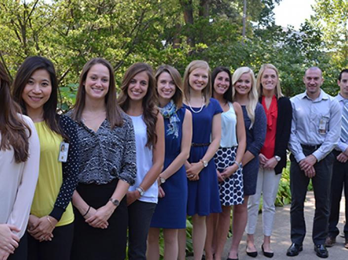 Image of twelve students in dress attire lines up in a row decending away from the camera smiling.  they are on a concrete path in a green wooded area with a large tree behind the first person on the left.  The sun is shining.
