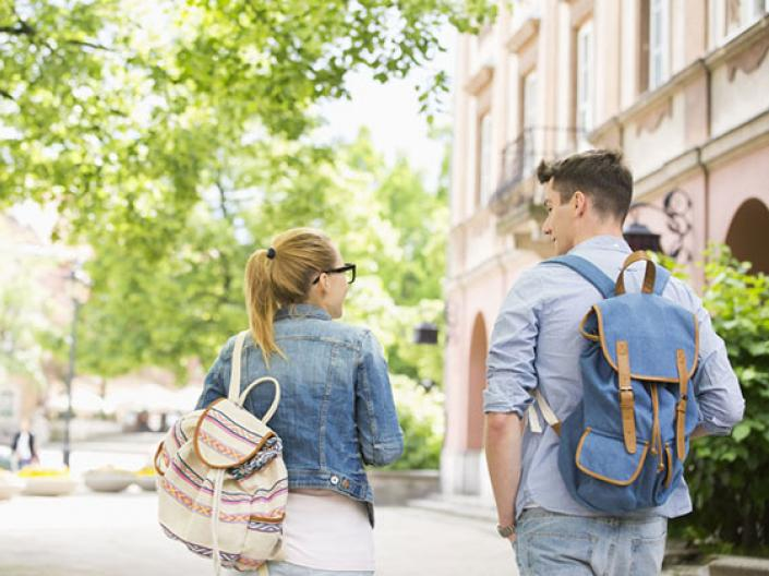 Image of two students walking away, with their backs to the camera, one wearing a jean jacket and white canvas backpack with brown and grey stripes and glasses, the other wearing a light blue shirt, jeans, and a denim fabric backpack with brown straps.  They are in the sun approaching a bright green tree on their left and a beige building on their right.  They are on a white path.