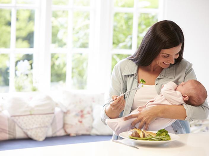 Image of mother holding baby with a plate of food in front of her on a large white counter, with brocolli a white meat on the plate.  the mother is holding a fork with a piece of brocolli on it and smiling down at the baby, with a large window and couch with white and pink patterned cushions behind her