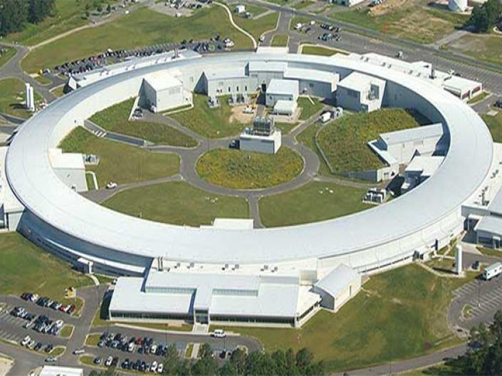Image of a white Synchrotron seen from the air, surrounded by roads, grass, parking lots and trees