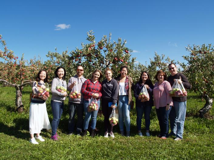 Image of 9 people standing in front of apple trees and holding bags of apples