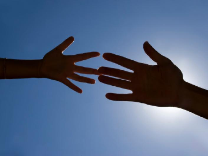 Two hands reaching out to each other, set against the blue sky