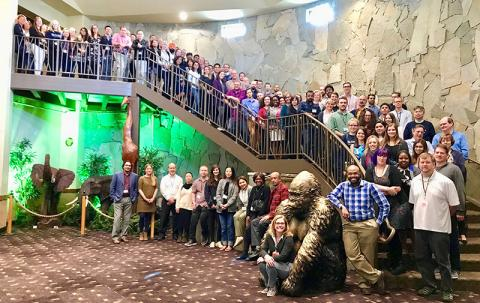 Department of pharmacology faculty and staff standing on staircase for group photo at annual retreat