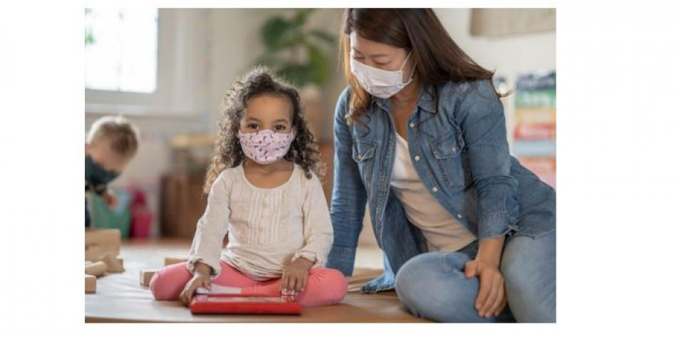 Small child and child care worker both wearing masks