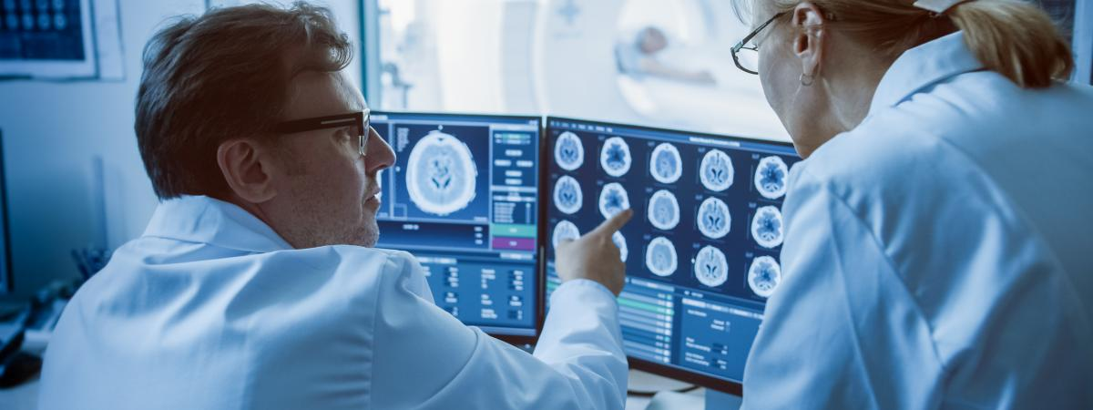 Two doctors review brain scans on computer screen