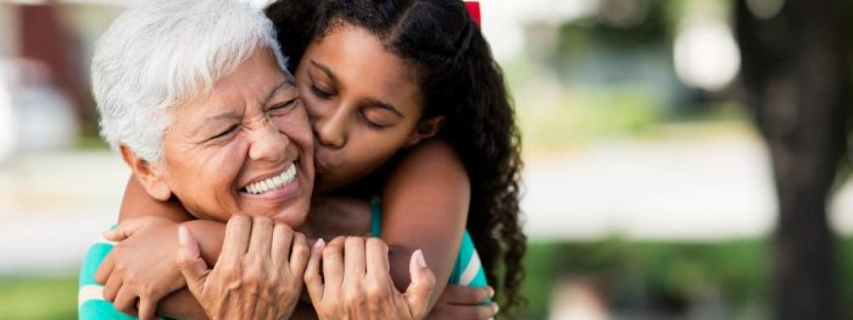 young grandaughter wrapping arms around grandmother's neck and kissing her cheek