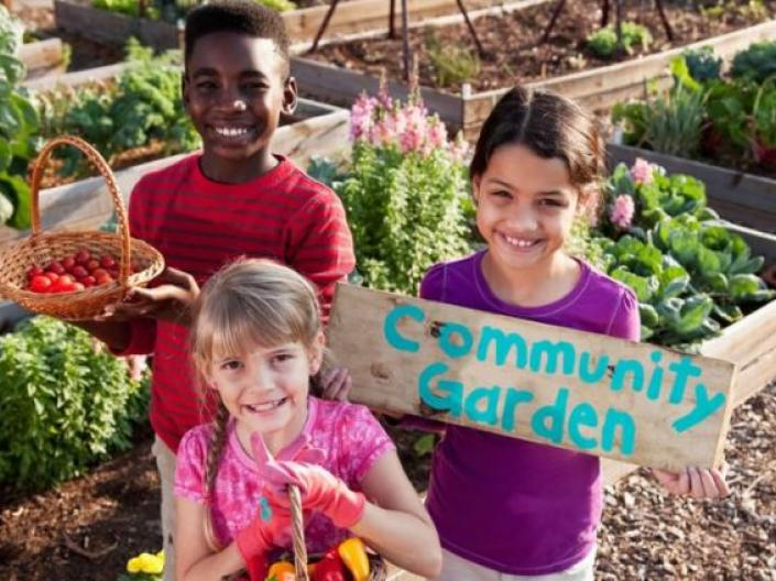 Children in a garden holding a garden holding a Community Garden sign