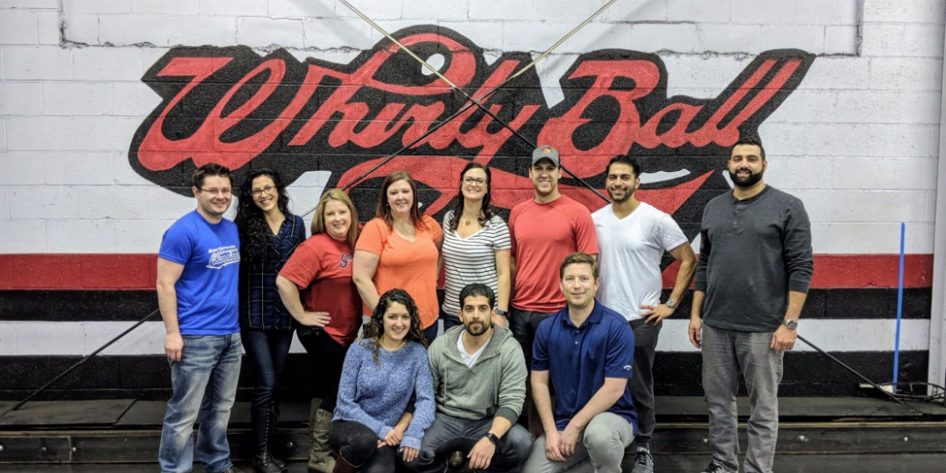 Group of people standing and kneeling in front of Whirly Ball sign