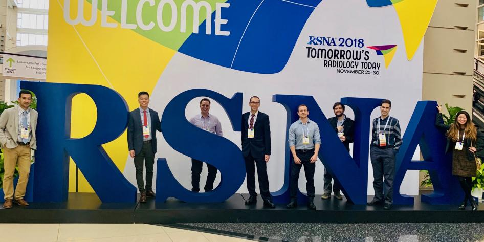 Large sign of RSNA Logo with row of radiology residents standing in front