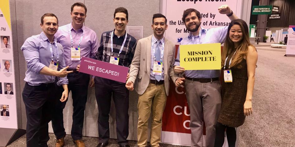 "Group of 6 radiology residents standing in a row holding signs ""we escaped""  and ""mission complete"""