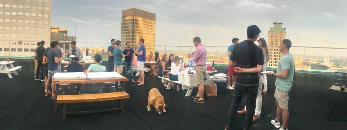 Standing residents on rooftop party with Cleveland skyline