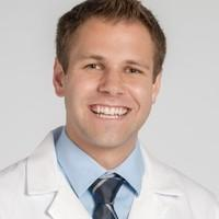 Headshot of medical student Aaron McBride in white coat and tie with grey background