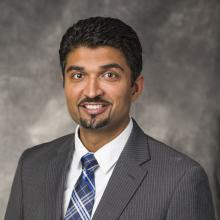 Headshot of Dr. Dan Patel in grey suit, blue striped tie, and grey background