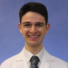 Headshot of medical student Paul Moiseyev with white coat, tie and light blue background