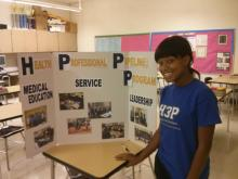 Taylor Moore, H3P alumna, prepares to present information on the club at an open house event.