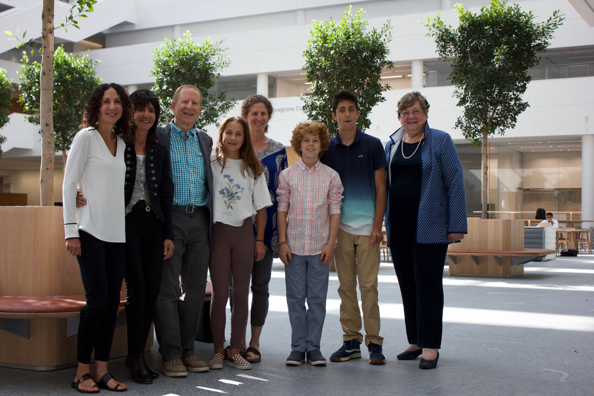 Photo line-up of Dr. Andrew Kaufman and his family with Dean Pamela Davis in the HEC