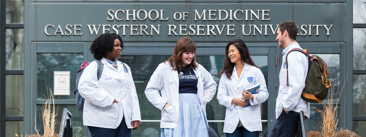 "Four CWRU School of Medicine medical students in white coats standing and talking in front of the School of Medicine doors with ""School of Medicine, Case Western Reserve University"" above."