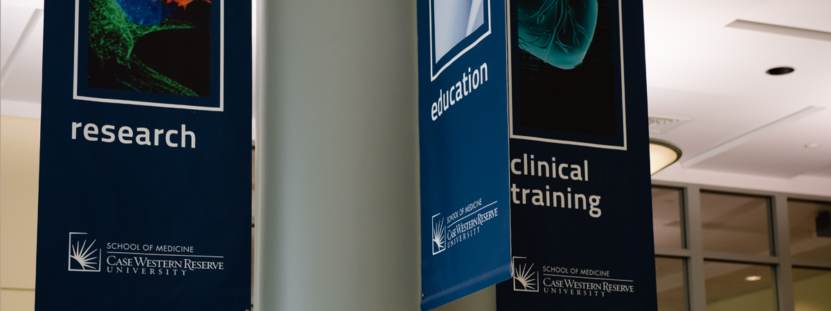 "Three hanging blue banners each with the School of Medicine logo at the bottom and displaying the word ""Research,"" ""Education,"" or ""Clinical Training."""