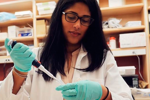 Female PREP scholar in white coat working with a pipette at a lab bench
