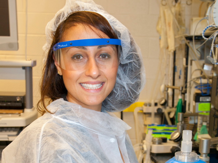 Alexandra McMillan in the CWRU Pathology and MSTP dressed in protective coat, gloves, and hair gear smiling and holding a blue canister